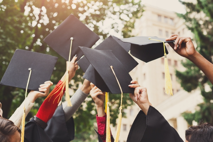 a-group-of-graduates-throwing-graduation-caps-in-VSQRGD2.jpg