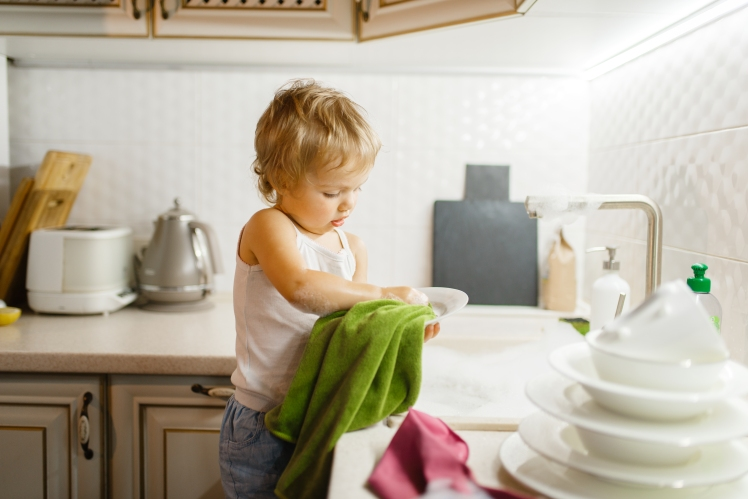 little-girl-wipes-the-dishes-on-the-kitchen-2MJ8HQU.jpg